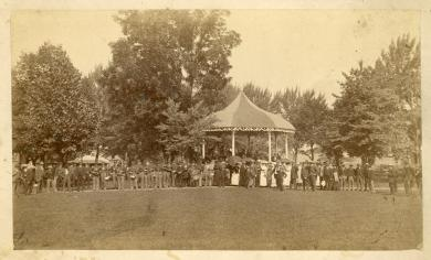 Line of visitors and band members in front of the band stand, c.1885