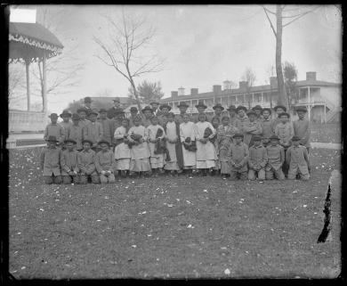 Group of Apache students with Richard Henry Pratt and two white men, c.1884