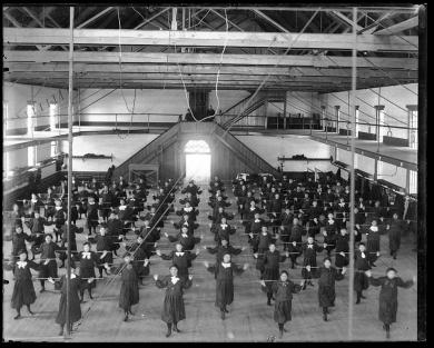 Female students in gymnasium with poles, c.1887
