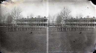 Male students lined up on school grounds with a child in a sleigh, c.1881