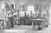 Male students posed in the tin shop with Richard Henry Pratt and instructor, c.1880