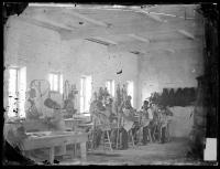 Instructor and students in the harness making shop, c.1882