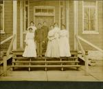 Seven students on steps of building, c.1900