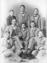 Seven male Crow students with John Nisely [version 2], c.1890
