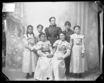 Five female students, one male student, and a female teacher, 1897