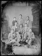 Seven male Crow students with John Nisely [version 1], c.1890