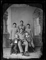 Four male students with two small white boys, c.1885